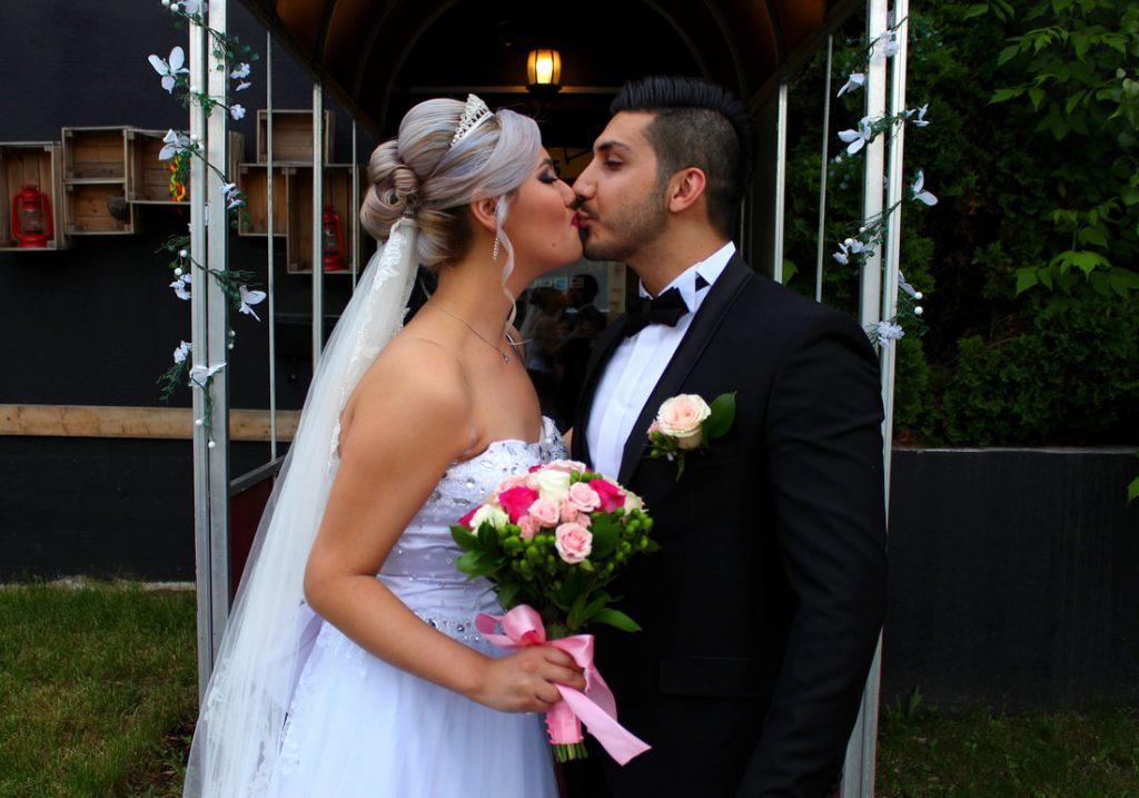 Jeunes mariés s'embrassant avec la femme tenant un bouquet
