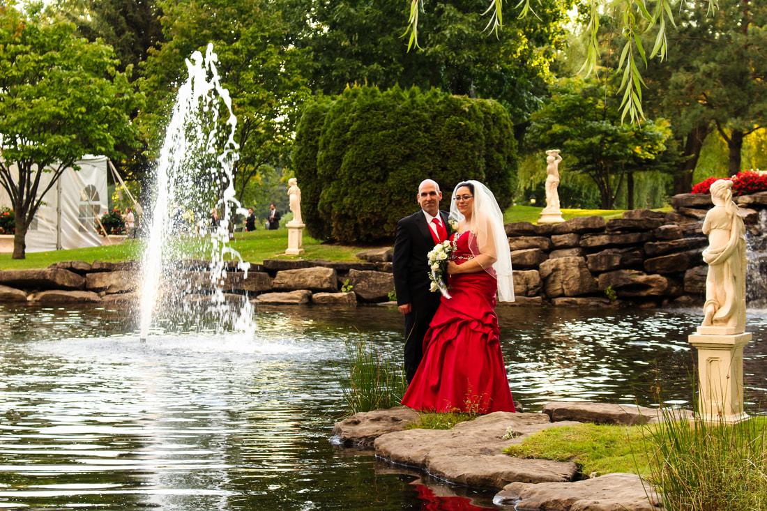 Bride and Groom posing in front of water basin