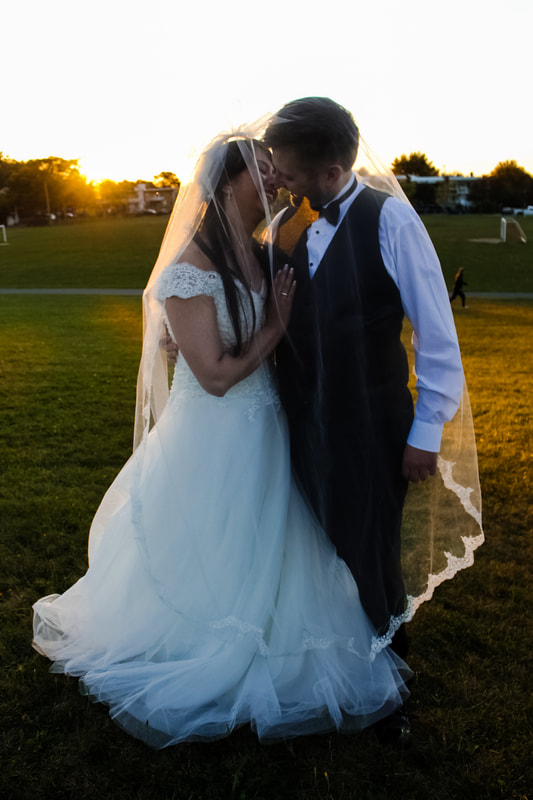 Bride and groom kissing on a background of setting sun