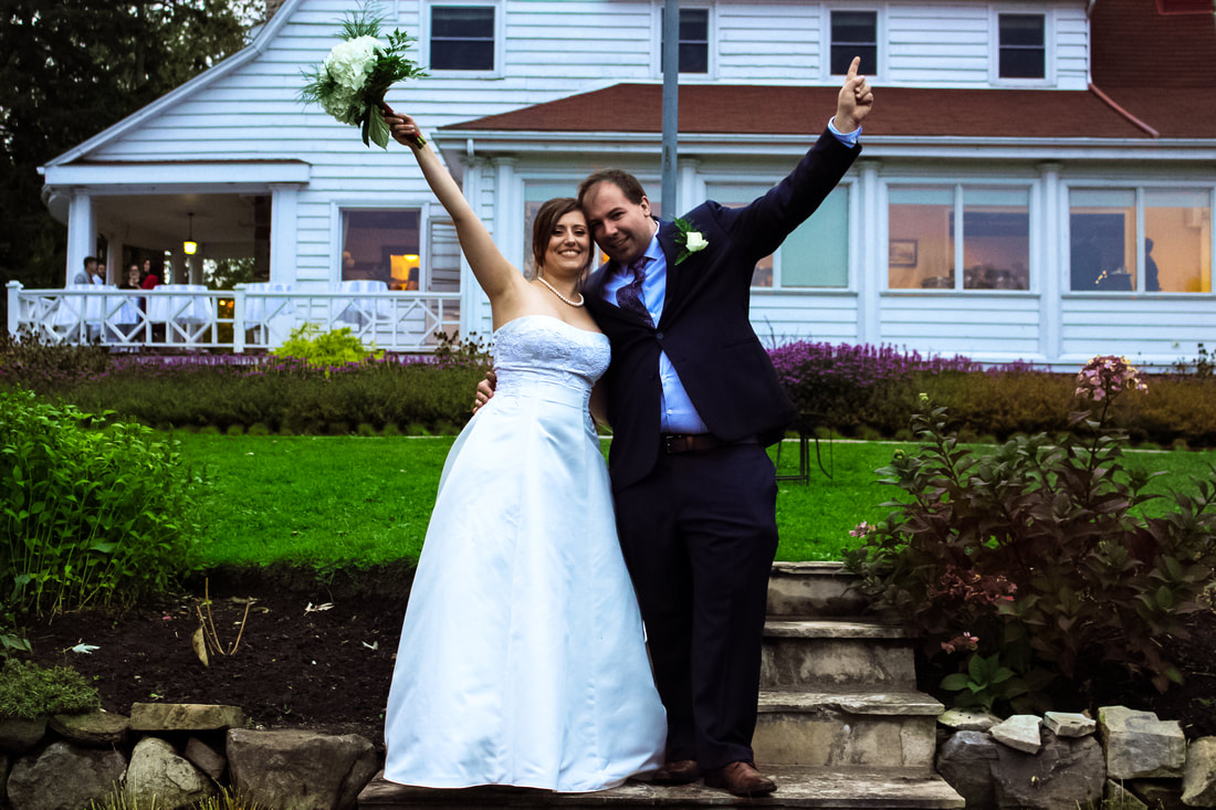 Bride and groom raising arms on stone staircase