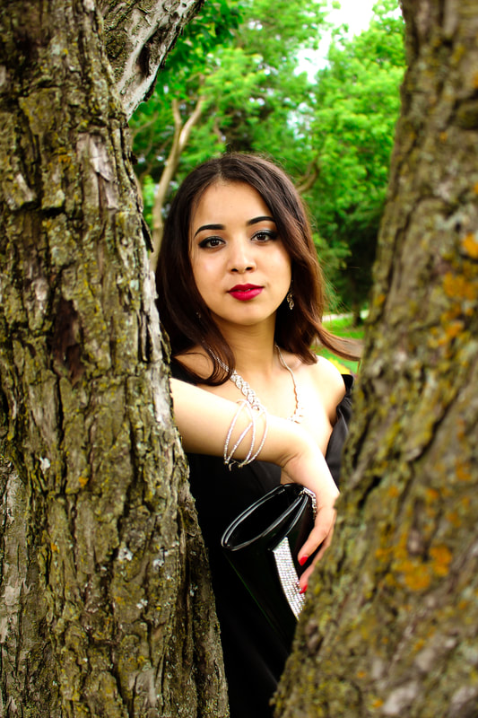 Woman portrait posing behind a tree