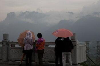 Personnes regardant les montagnes au loin par temps de pluie