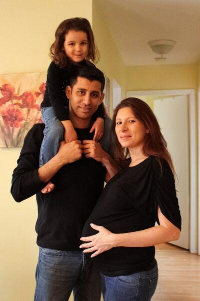 Couple dont la femme est enceinte et père portant sa fille susr ses épaules