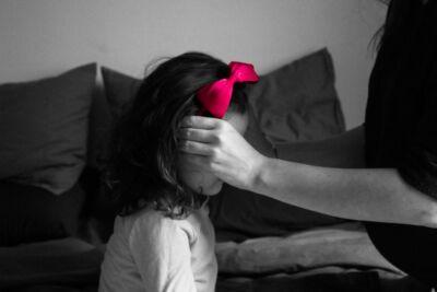 Photo noir et blanc d'une mère ajustant le ruban rose dans les cheveux de sa fille
