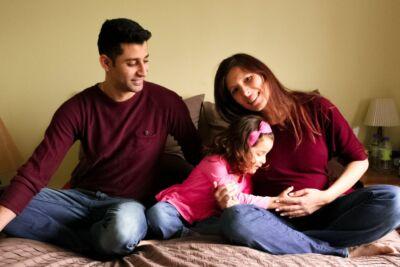 Couple avec fille qui touche le ventre de sa mère enceinte