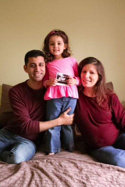 Couple souriant avec leur fille entre les deux