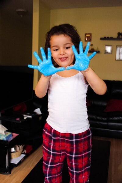 Jeune fille souriant avec ses deux mains enduites de peinture bleue