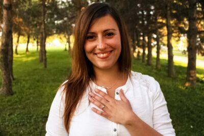 Portrait d'une jeune femme souriante au milieu d'arbres