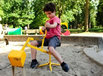 Jeune garçon jouant avec une pelle mécanique dans un bac à sable