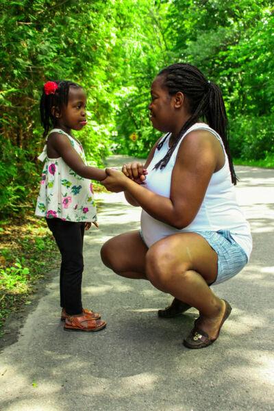 Mère et sa fille se faisant face. La mère tient la main de sa fille