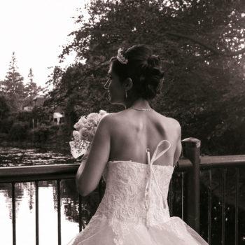 Jeune femme en robe de mariage tenant le bouquet sur un pont