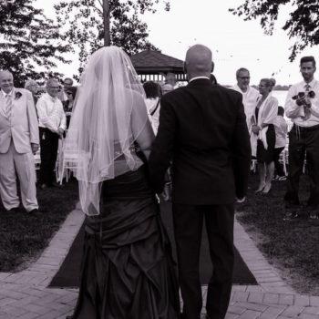 Photo noir et blanc avec mariés tournant le dos au photographe
