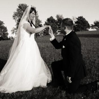 Mariés dans un champ avec époux genou à terre