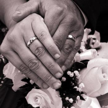 Gros plan sur les mains de mariés et leurs alliances