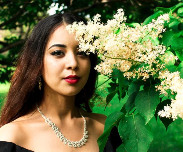 Jeune femme élégante devant une branche fleurie