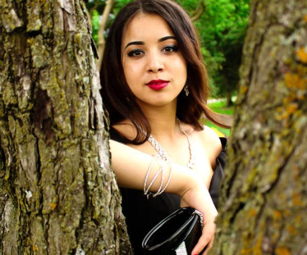Jeune femme élégante posant entre deux troncs d'arbres
